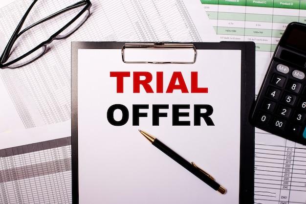 L'offre d'essai est écrite sur une feuille de papier blanc, près des verres et de la calculatrice.