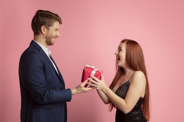 Offrir un cadeau. célébration de la saint-valentin, heureux couple caucasien isolé sur fond de studio de corail. concept d'émotions humaines, expression faciale, amour, relations, vacances romantiques.