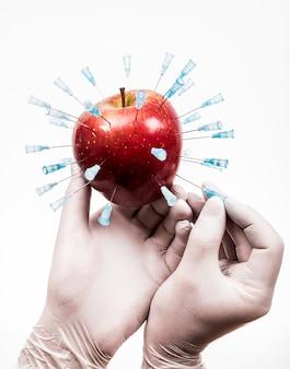 Ogm apple. main d'injection de produit chimique à la pomme.