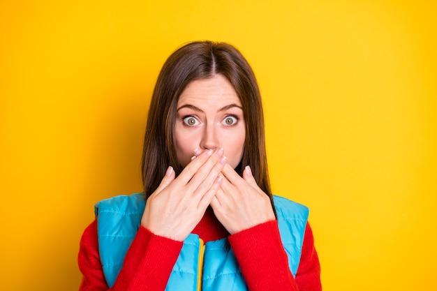 Oh incroyable. portrait en gros plan d'une fille choquée qui dit que ses amis se sentent coupables secrètes fermer les mains de couverture les lèvres portent un chandail de saison isolé sur un fond de couleur brillante et brillante
