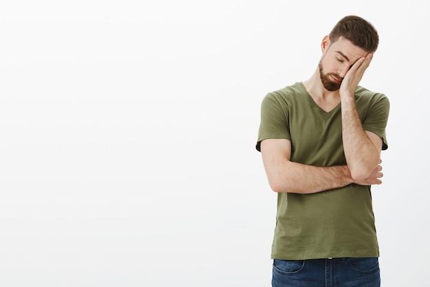 Oh mon dieu comme c'est fatiguant. portrait d'homme fatigué et drainé bourreau de travail avec barbe s'appuyant sur la paume comme faisant facepalm signe, fermer les yeux épuisés et drainés posant bouleversé et mal à l'aise sur un mur blanc