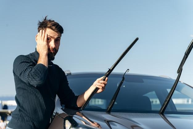Oh mon dieu. un homme de race blanche tient sa tête avec des émotions choquées tout en changeant les essuie-glaces d'une voiture. notion de transport