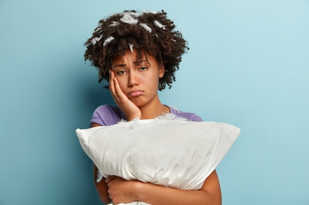 Oh non, dors. une femme noire surmenée mécontente touche la joue, regarde avec une expression sombre, tient étroitement l'oreiller blanc, a une expression malheureuse après un mauvais repos, pose sur un mur bleu