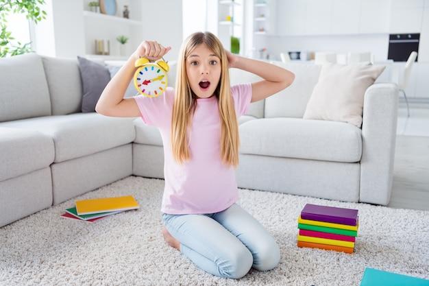 Oh non, je manque la leçon en ligne. photo pleine taille d'une enfant frustrée étonnée s'asseoir sur un tapis de sol tenir l'horloge tactile main tête crier omg dans la maison à l'intérieur