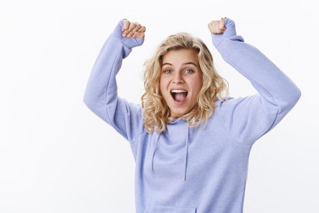 Oh oui bébé. portrait d'une femme séduisante joyeuse et joyeuse, heureuse et excitée, aux cheveux courts et aux yeux bleus, criant oui du bonheur célébrant la victoire, levez les mains dans la joie et le triomphe