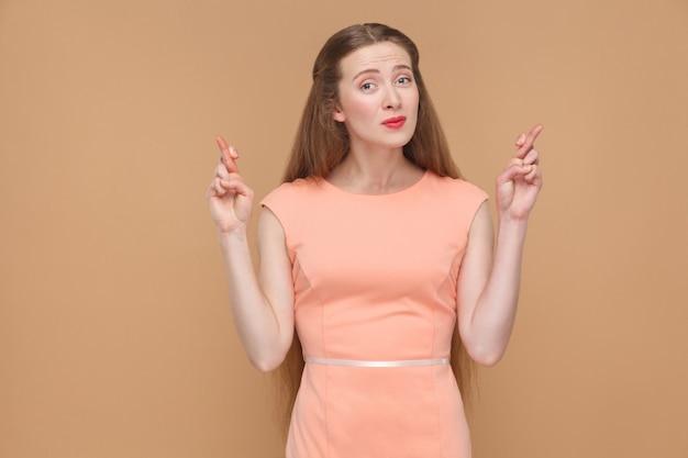 Oh s'il vous plait. femme pleine d'espoir avec les doigts croisés en regardant la caméra. émotionnelle mignonne, jolie femme avec du maquillage et des cheveux longs en robe rose, prise de vue en studio, isolée sur fond marron clair ou beige.