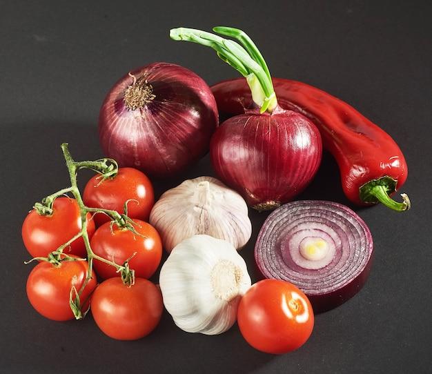 Oignon et ail et piments forts et tomates isolés sur fond noir.