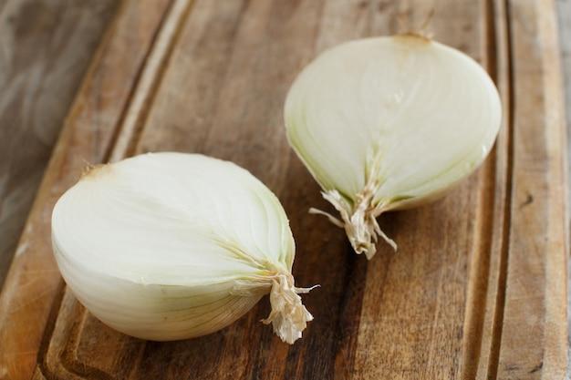Oignon blanc cru frais tranché sur la planche de cuisson