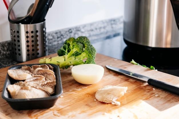 Oignon avec un couteau champignons et chou dans une cuisine.