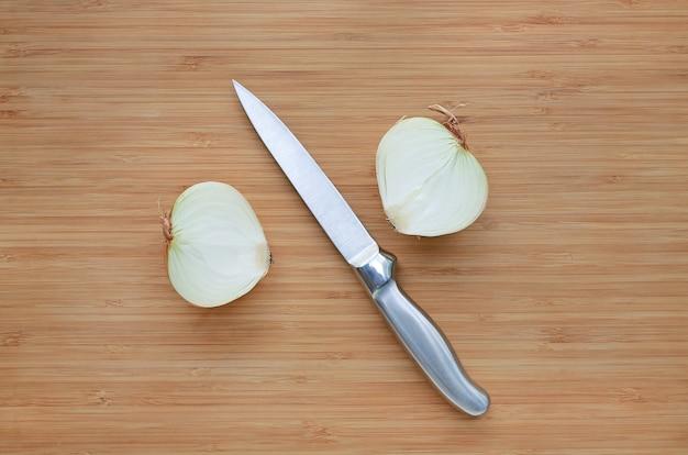 Oignon frais coupé à moitié avec un couteau tranchant sur fond de planche de bois.