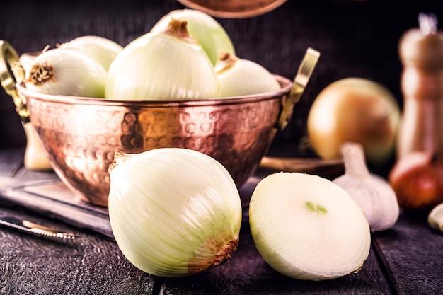 Oignon haché coupé en deux, avec des ustensiles de cuisine en cuivre en surface, cuisine rurale ou rustique