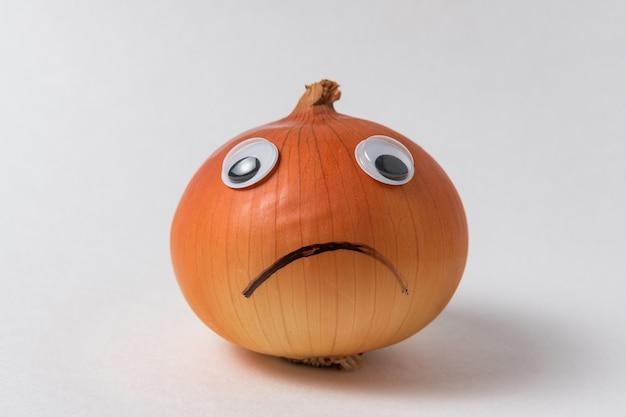 Oignon napiforme au visage triste. oignon bulbe aux yeux écarquillés et sourire triste sur fond blanc