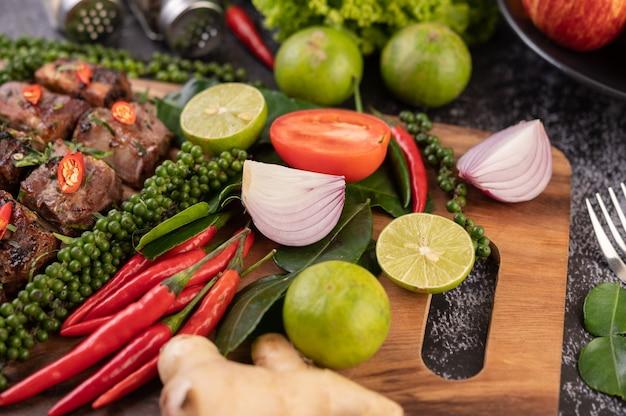 Oignon, piment, poivre frais feuilles de lime kaffir et citron vert placés sur une planche à découper en bois.