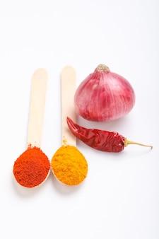 Oignon, piment rouge, poudre de piment rouge et poudre de curcuma sur une surface blanche