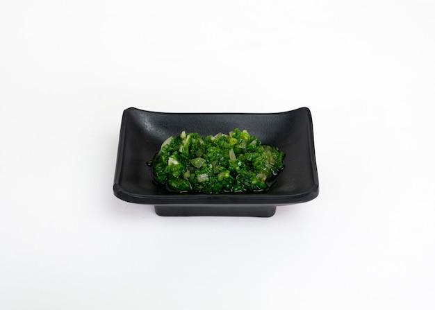 Oignon de printemps haché ou sauce à la ciboulette marinée dans une tasse noire