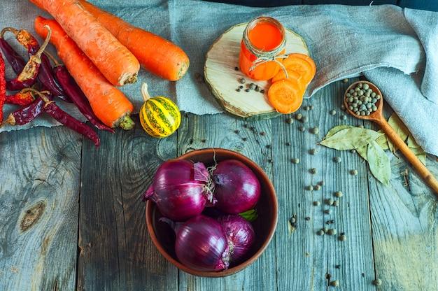 Oignon rouge dans un bol d'argile parmi des légumes et des épices