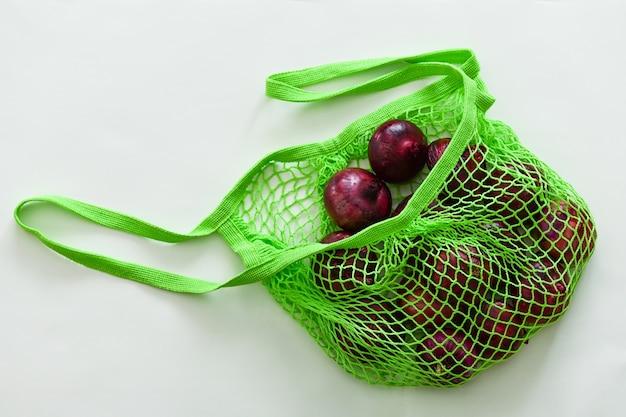 Oignon rouge dans un sac de ficelle verte sur une surface grise