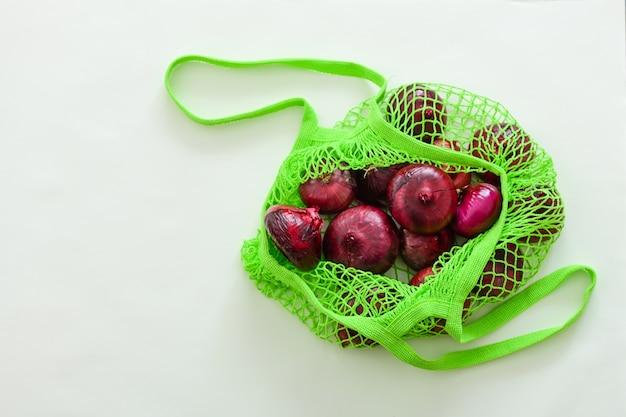 Oignon rouge dans un sac de ficelle verte sur une table en bois