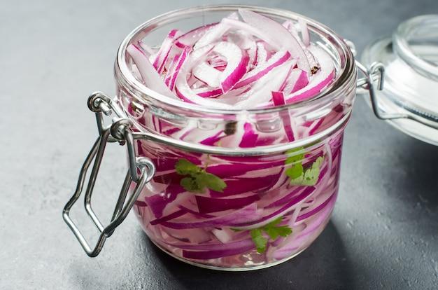 Oignon rouge haché mariné au vinaigre dans un bocal en verre. un délicieux accompagnement pour les plats de viande et de poisson. fond gris clair.