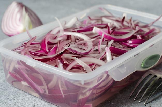 Oignon rouge haché mariné au vinaigre dans un récipient en plastique. un délicieux accompagnement pour les plats de viande et de poisson. fond gris clair.
