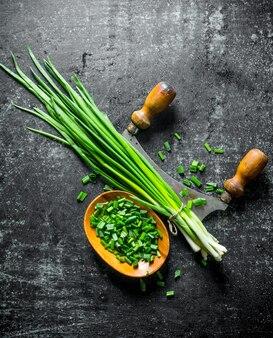 Oignon vert haché dans une assiette en bois avec un couteau sur une table rustique sombre