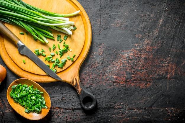 Oignon vert haché sur une planche à découper avec un couteau. sur fond rustique foncé