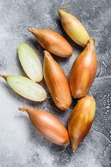 Oignons échalotes jaunes, coupés en deux.