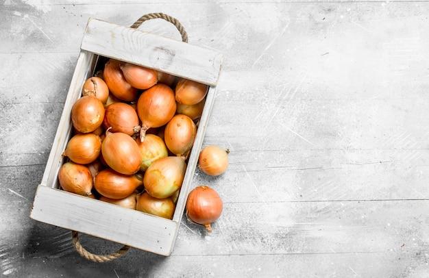 Oignons frais dans la boîte. sur table rustique