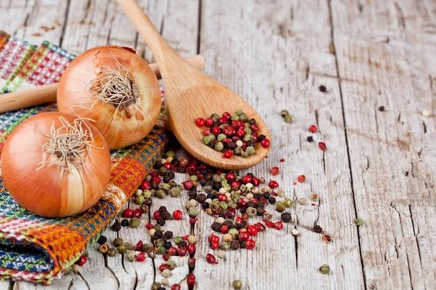 Oignons frais et grains de poivre dans une cuillère