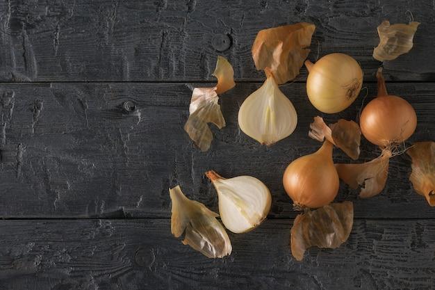 Oignons frais pelés et non pelés sur une table en bois.