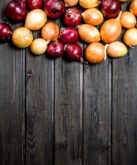 Oignons frais rouges et jaunes. sur fond de bois