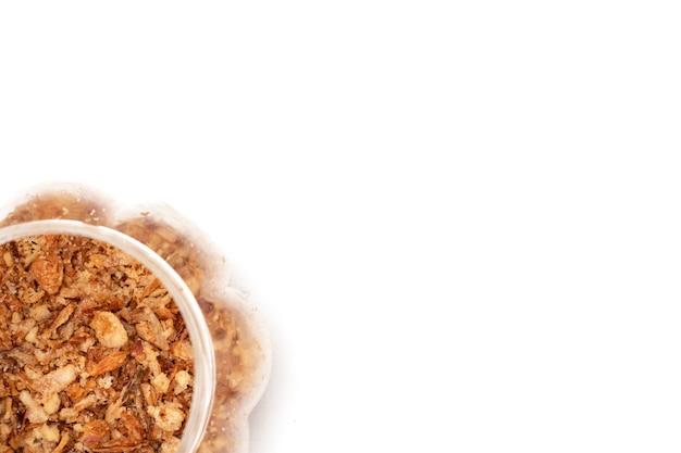 Oignons frits dans un bocal sur fond blanc