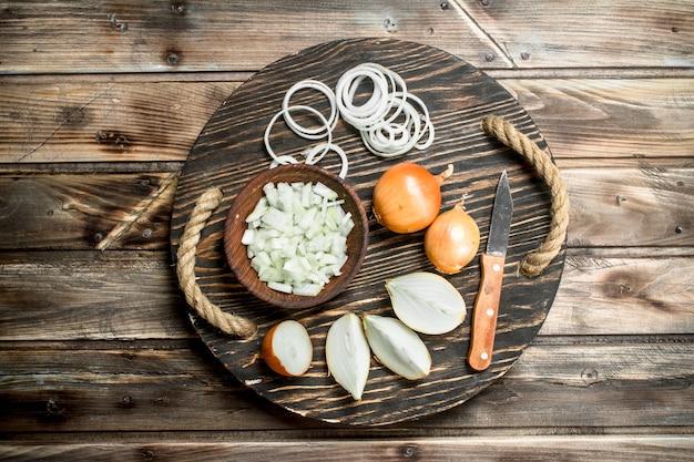 Oignons hachés dans un bol et morceaux d'oignons sur le plateau avec un couteau. sur bois