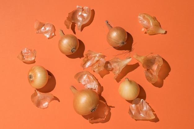 Oignons mûrs frais et cosses d'oignon sur fond orange. récolte d'automne. espace pour le texte. mise à plat.