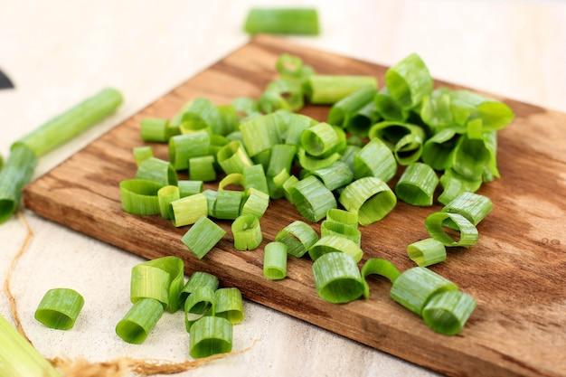 Oignons de printemps tranchés et hachés, oignons à salade, oignons verts ou oignons verts sur planche à découper en bois, cuisson étape par étape