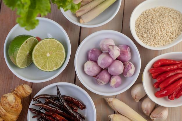 Oignons rouges, citron, citronnelle, piments, ail, galanga et laitue dans une tasse sur un plancher en bois.