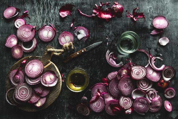 Oignons rouges coupés en tranches sur un fond noir dans un style rustique