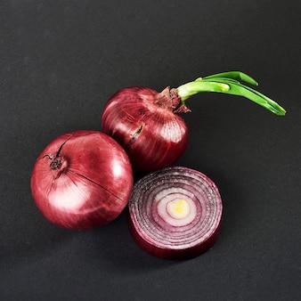 Oignons rouges entiers, isolés sur fond noir