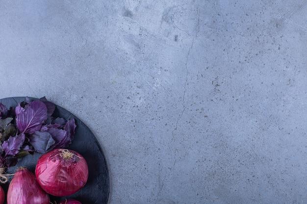 Oignons rouges, radis et basilic frais sur une planche à découper noire.