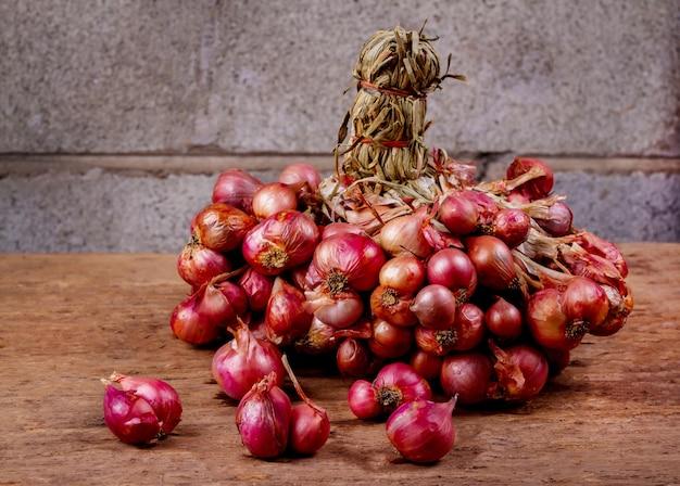 Oignons rouges sur la vieille table en bois vintage