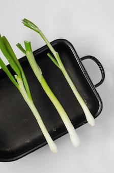 Oignons verts au centre sur un concept de nourriture crue ingrédient sain plat de four noir