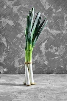 Oignons verts ou échalotes sur une table en béton gris