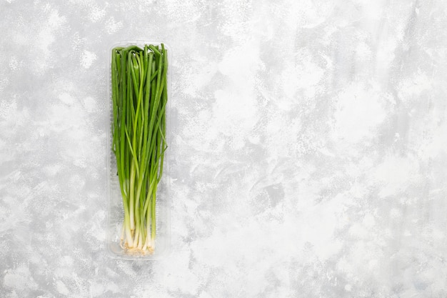 Oignons verts frais dans une boîte en plastique sur du béton gris