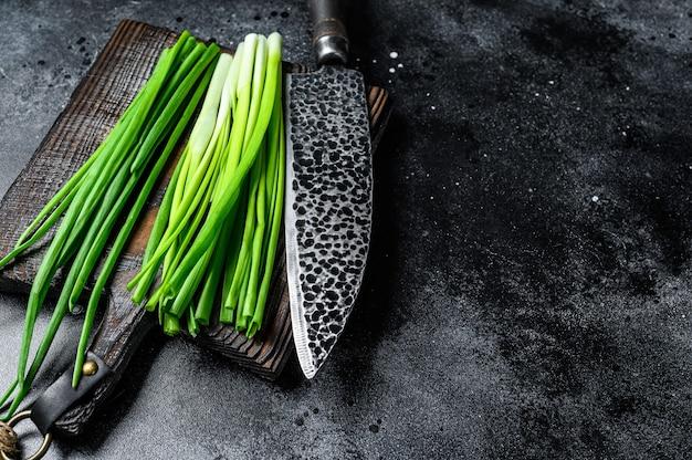 Oignons verts frais sur une planche à découper. fond noir. vue de dessus. espace de copie.