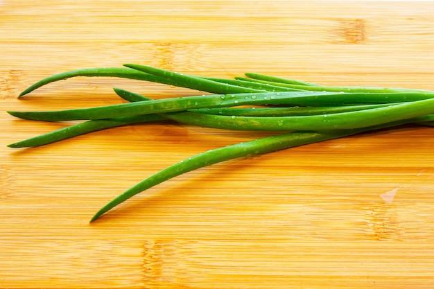 Oignons verts frais sur une planche à découper. gouttes d'eau sur un oignon vert fraîchement coupé. nutrition adéquat