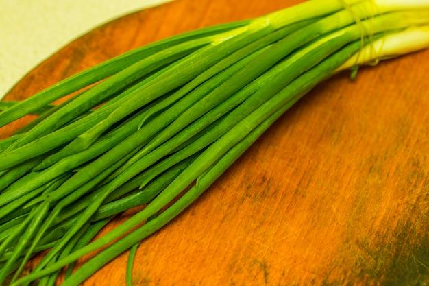 Oignons verts frais sur une planche à découper