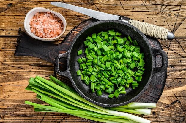 Oignons verts tranchés dans une casserole. fond en bois. vue de dessus.