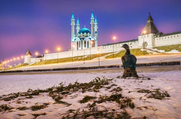 Un oiseau de branches se dresse dans la neige près du kremlin de kazan un soir d'hiver