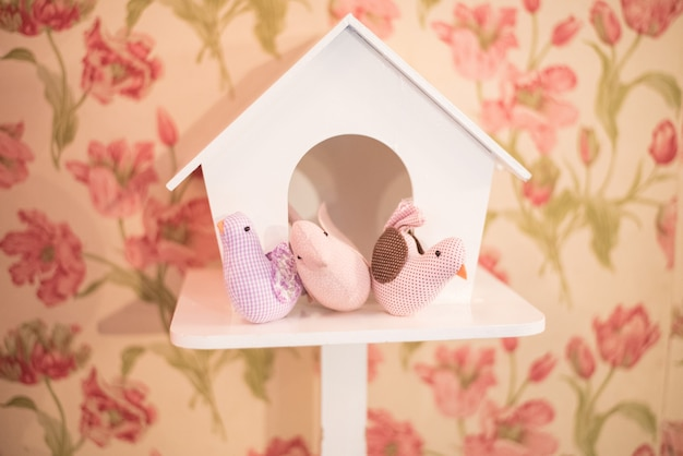 Oiseaux jouets dans une maison en bois