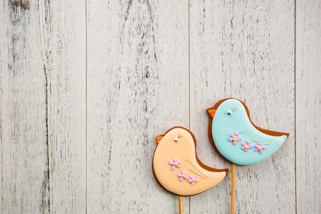 Oiseaux de pain d'épice de pâques sur une table en bois blanche avec espace de copie. thème de la cuisson au printemps